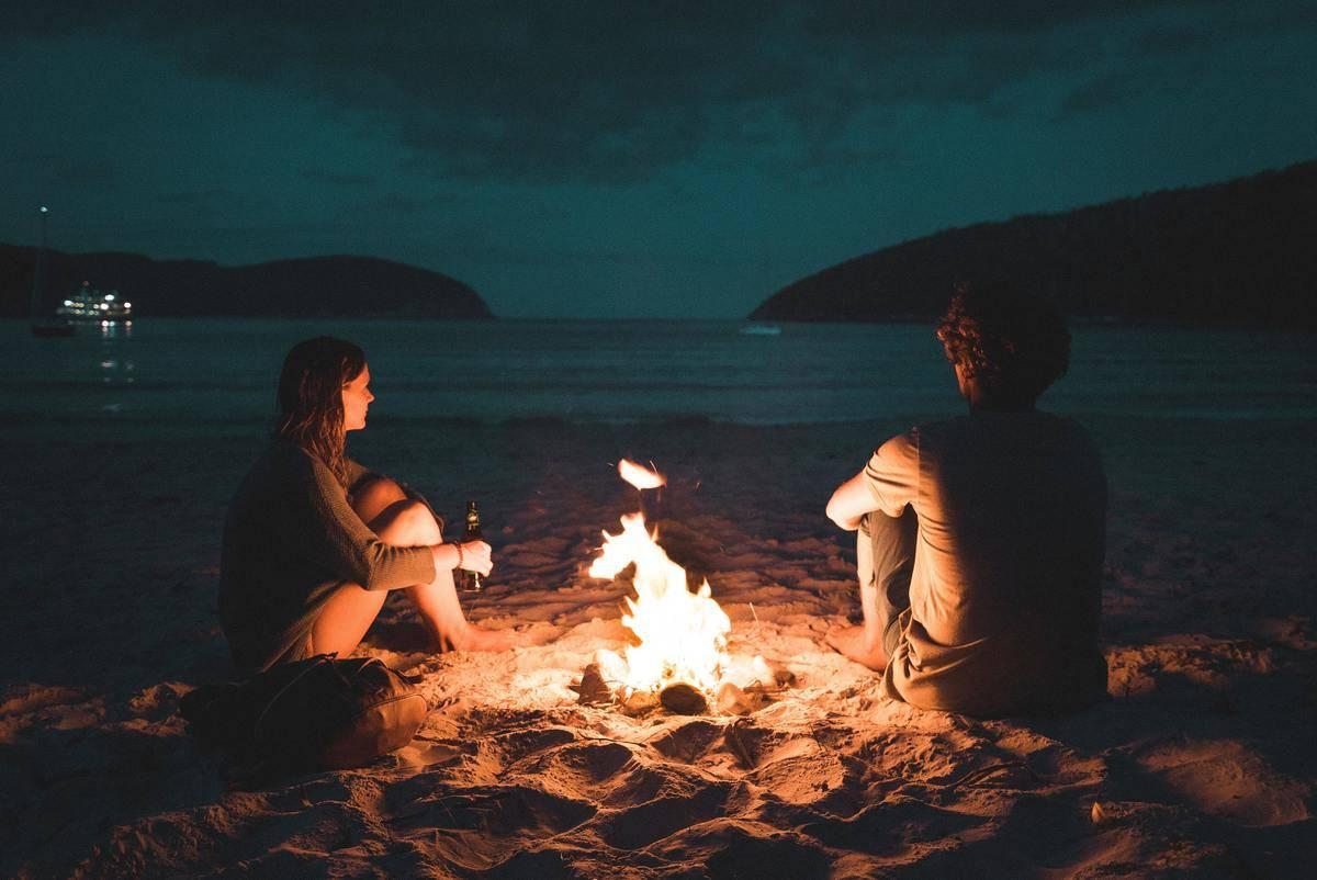 couple sits at bonfire at the beach