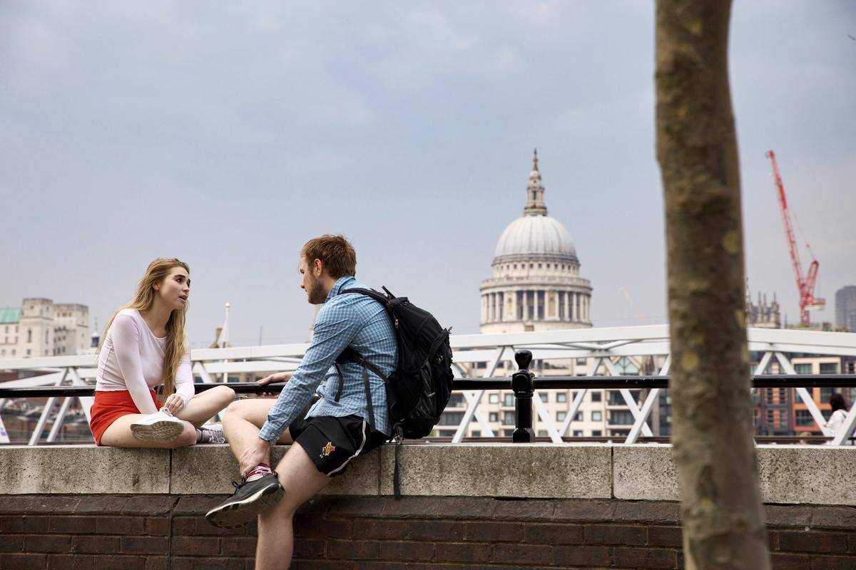 man and woman sitting on concrete wall, talking