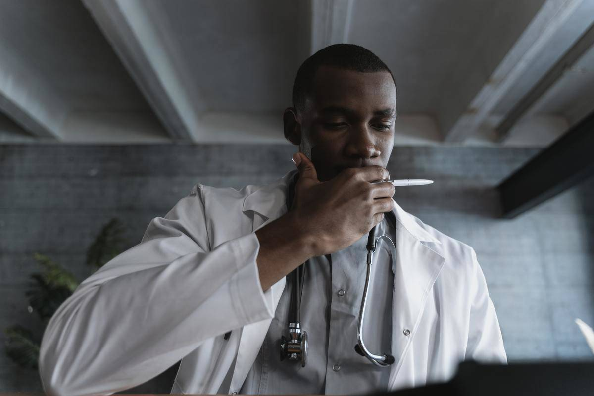 doctor looking at report with hand over his mouth