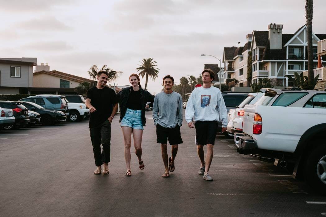 group of 3 guys and one girl walking in a parking lot in California