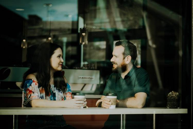 man and woman sitting inside a coffee shop having a discussion and smiling
