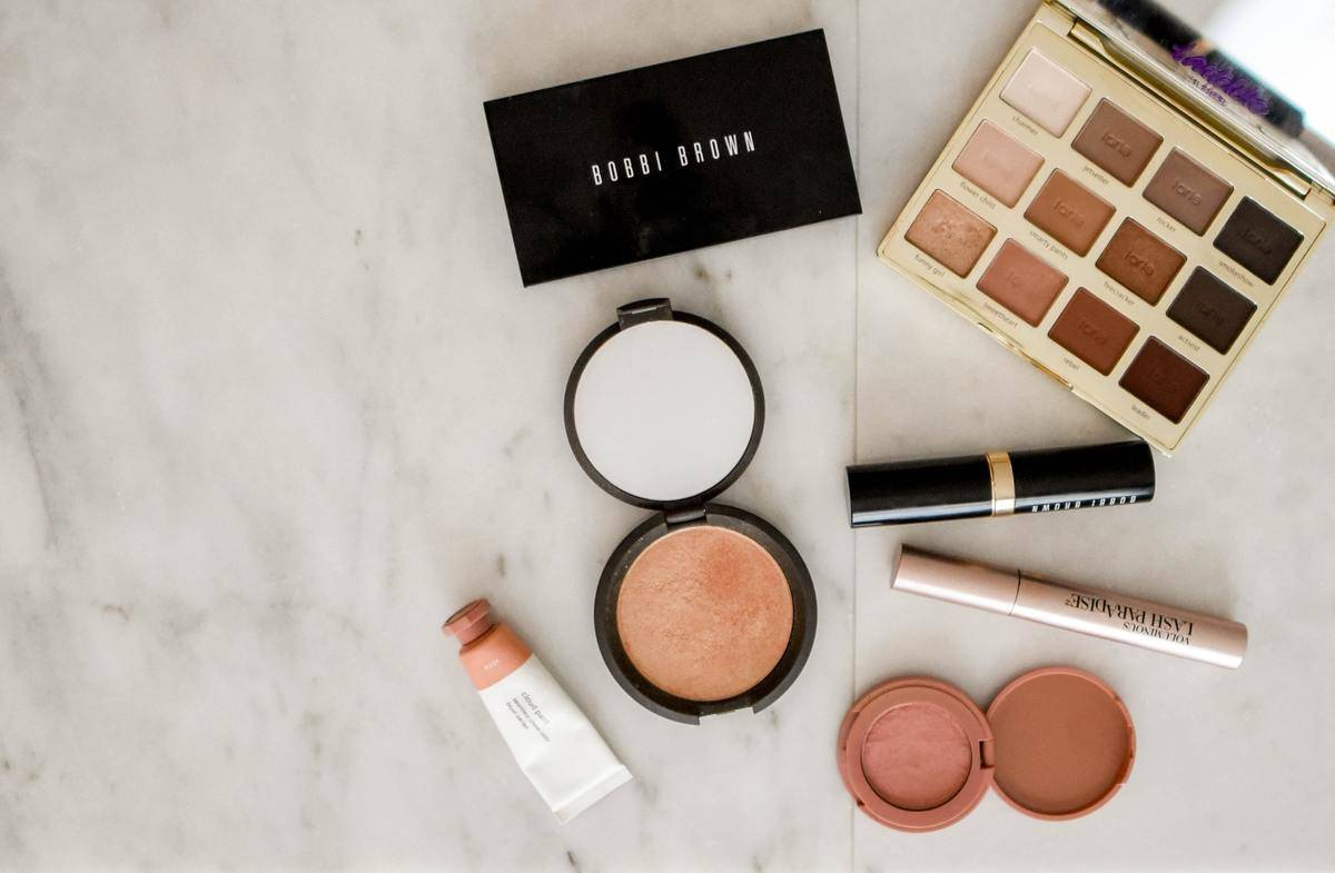 makeup compacts and palettes on marble countertop