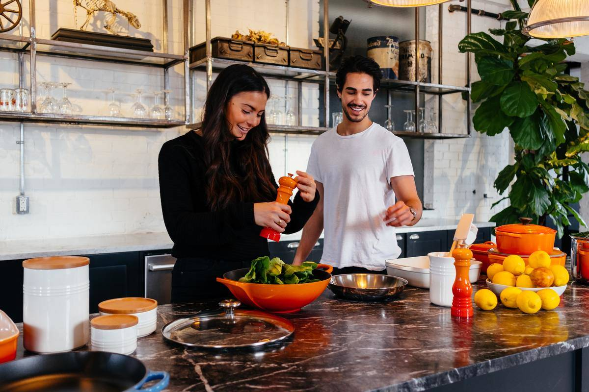 man and woman cooking on kitchen island