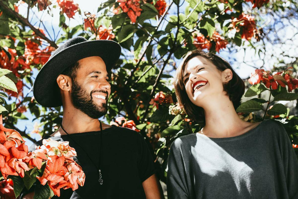 man and woman laugh by a tree