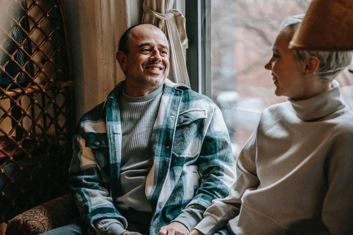 man and woman sit at window talking