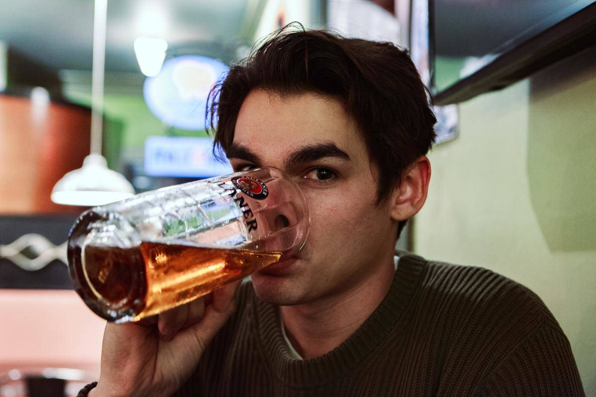 man drinking out of beer glass