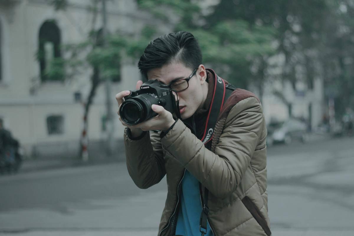 man holding up camera taking photo outside