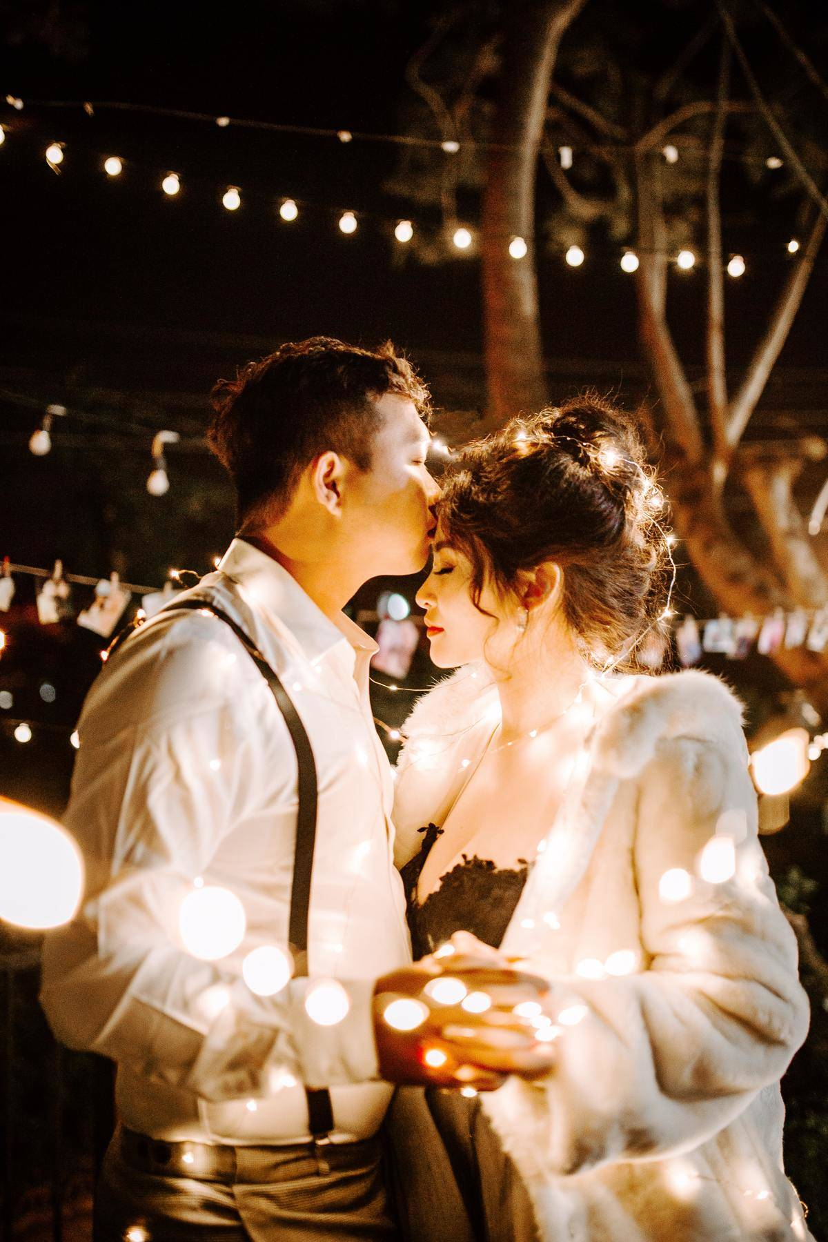 man kisses woman while slow dancing surrounded by string lights