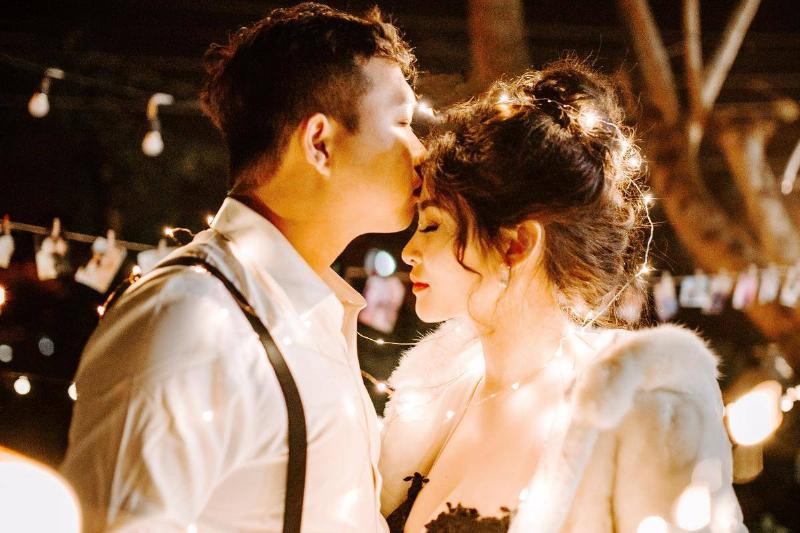 man kisses woman's forehead as they slow dance in romantic lighting