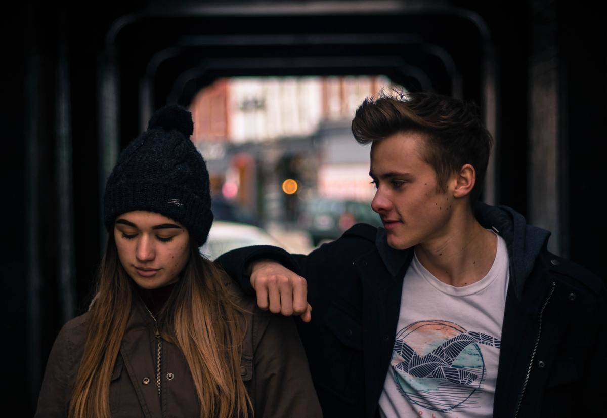 men leaning on shoulder of woman looking down