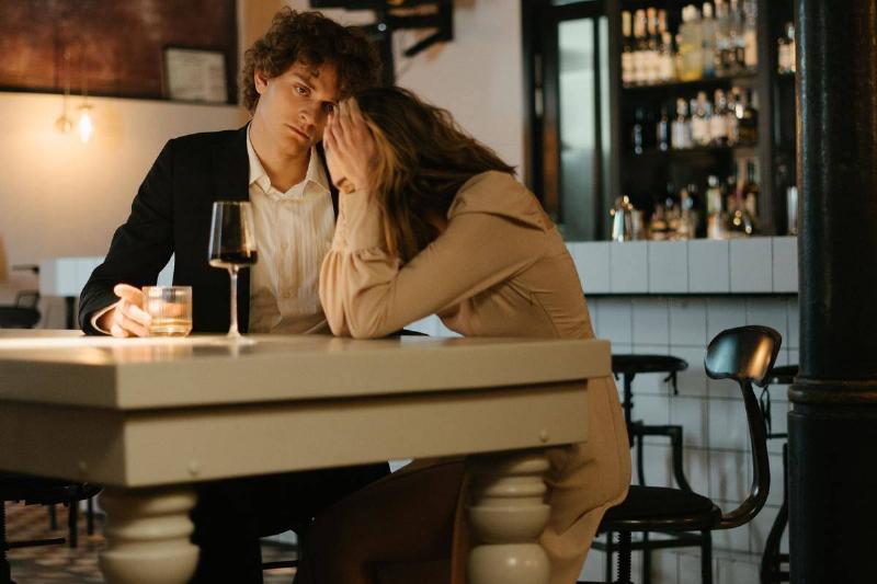man looks at woman as they sit at bar