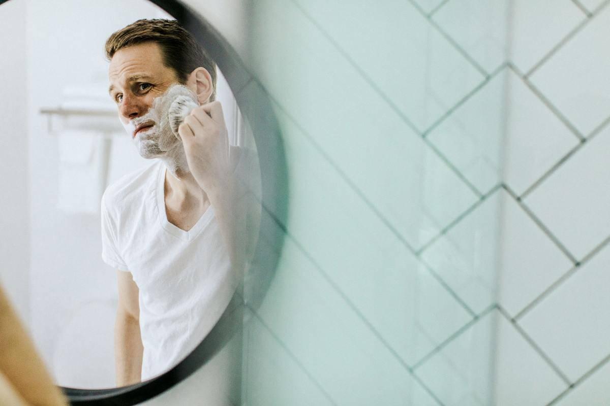 man shaving in mirror reflection