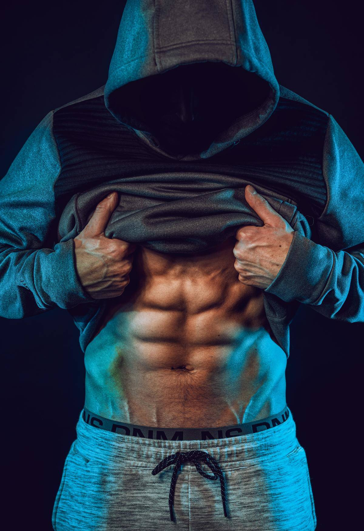 man shows off abs under his shirt