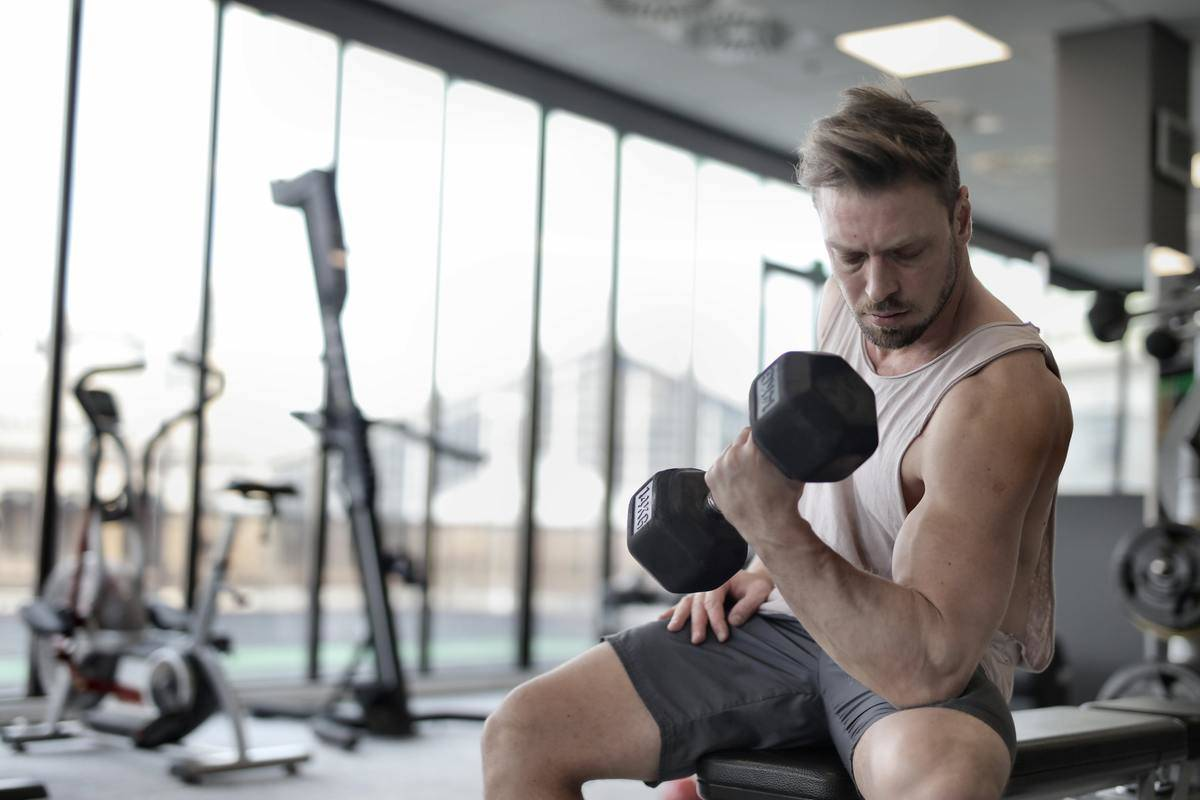 man shows off bicep on workout bench