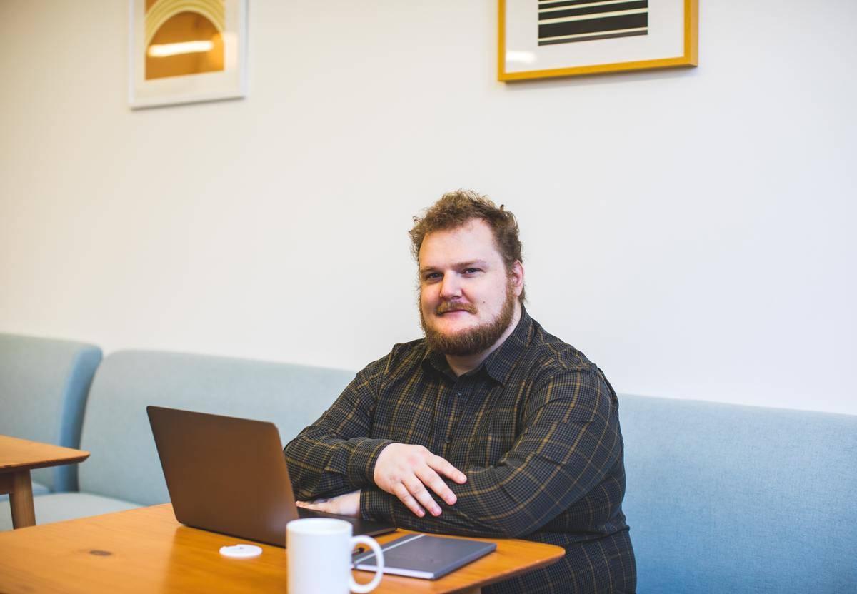 man sits at desk wit laptop smiling