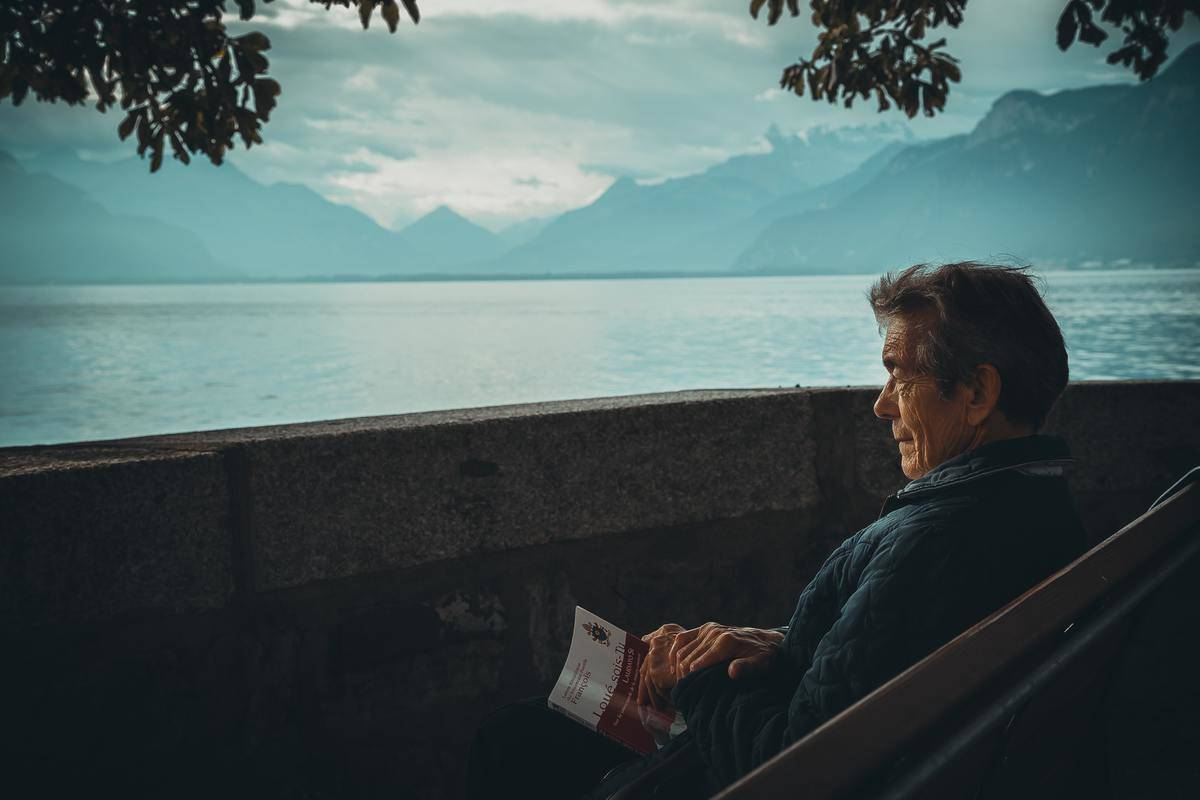 man sits on bench by the water