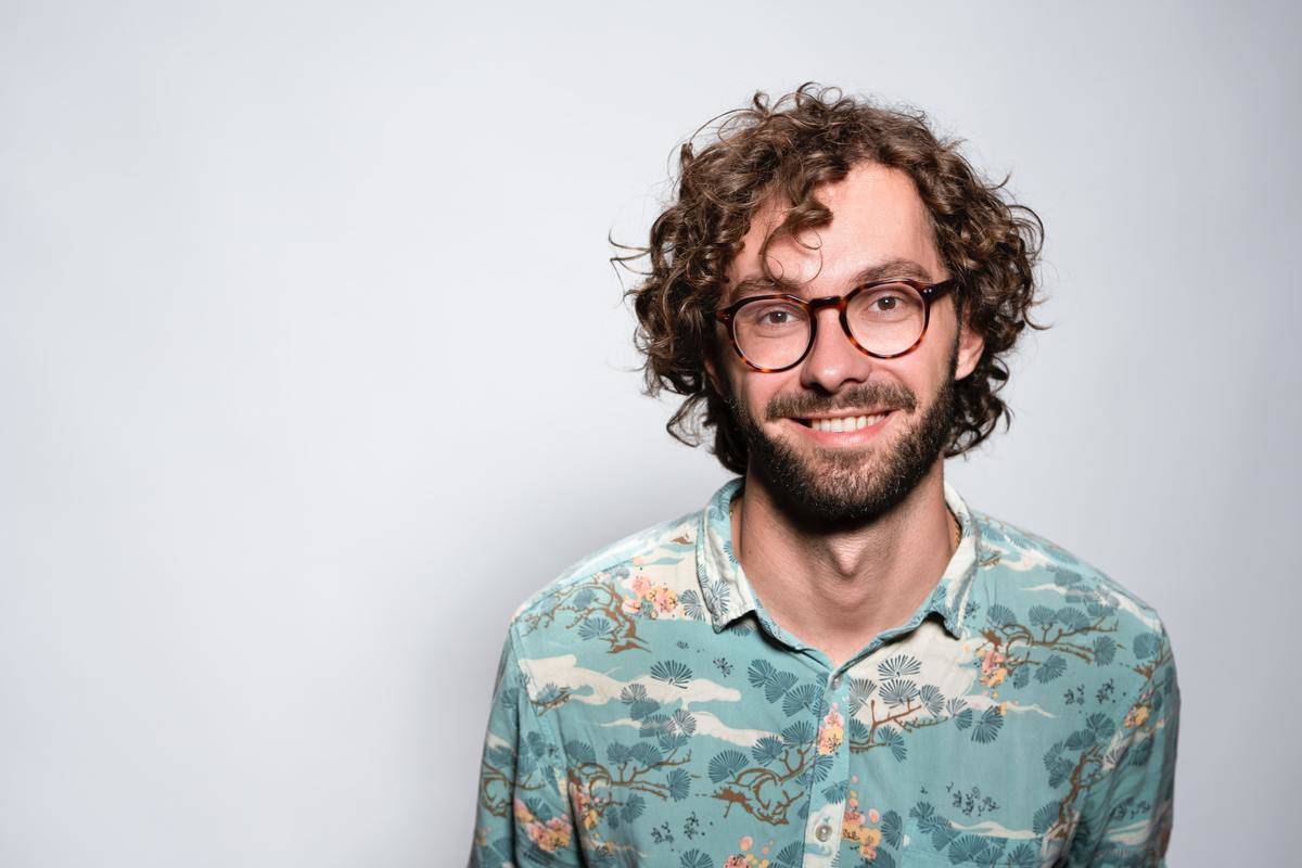 man smiling in glasses and floral shirt