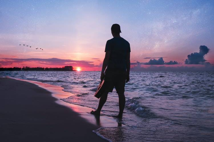 silhouette of man standing staring at the sunset