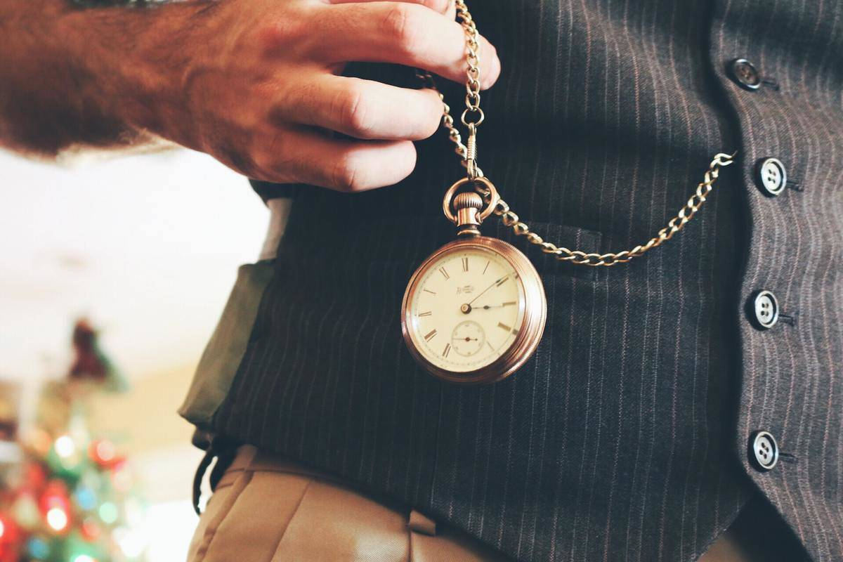 man takes out pocket watch from vest