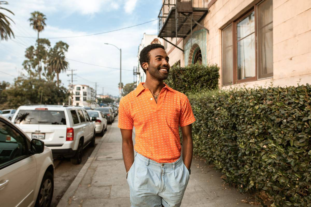man with hands in pockets walking on sidewalk