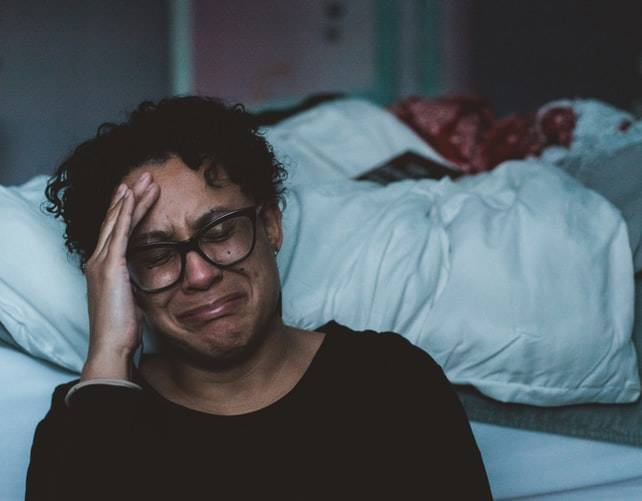 crying woman with her head in her hand sitting against the foot of her bed