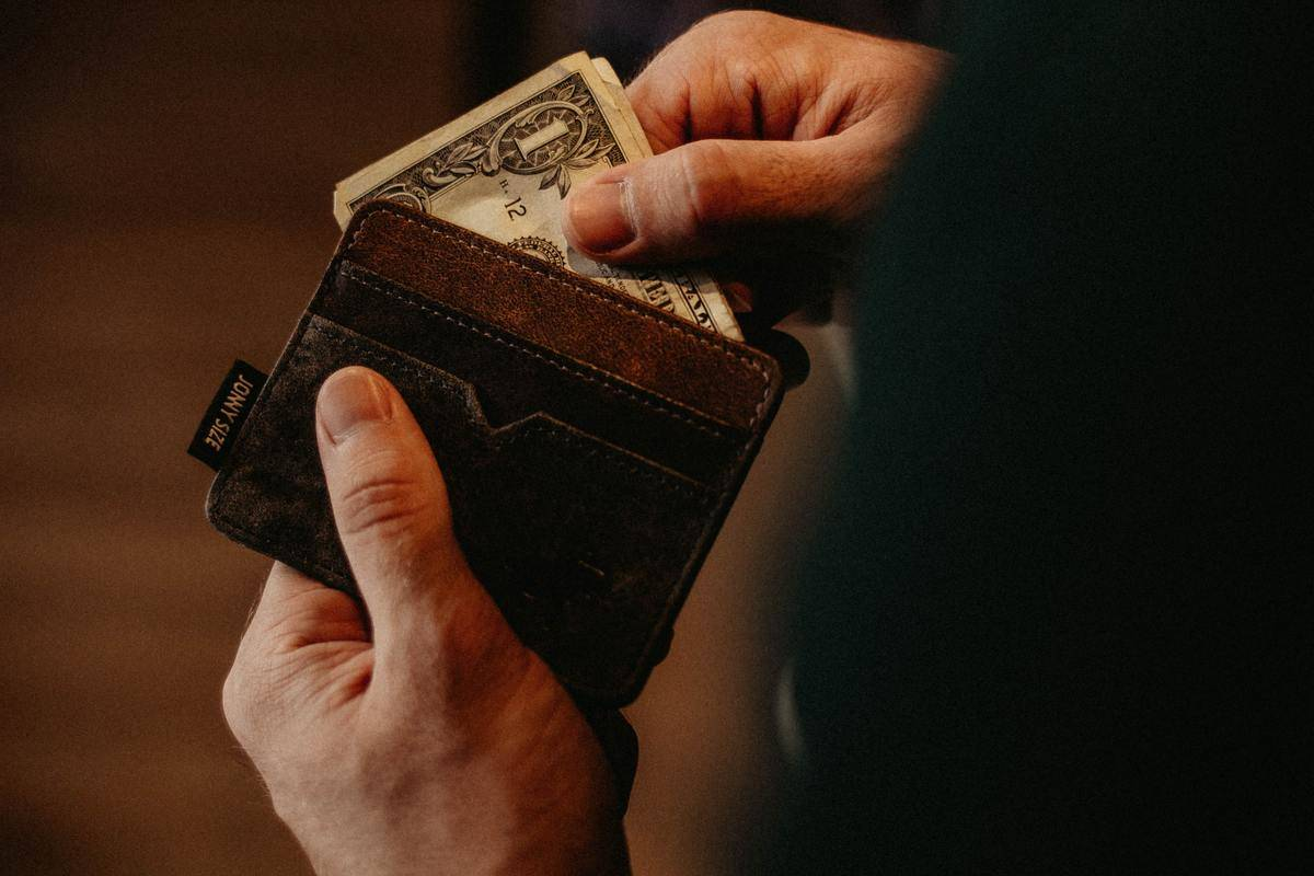hand taking out bills from wallet