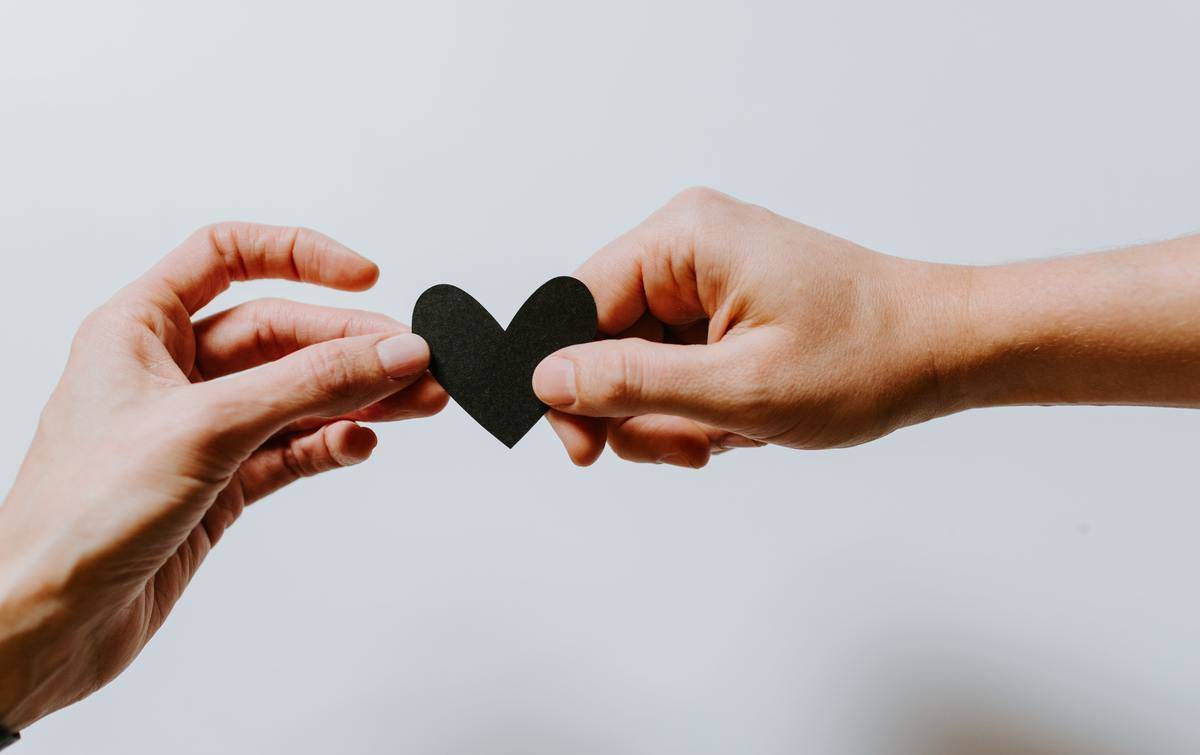 two people holding paper heart