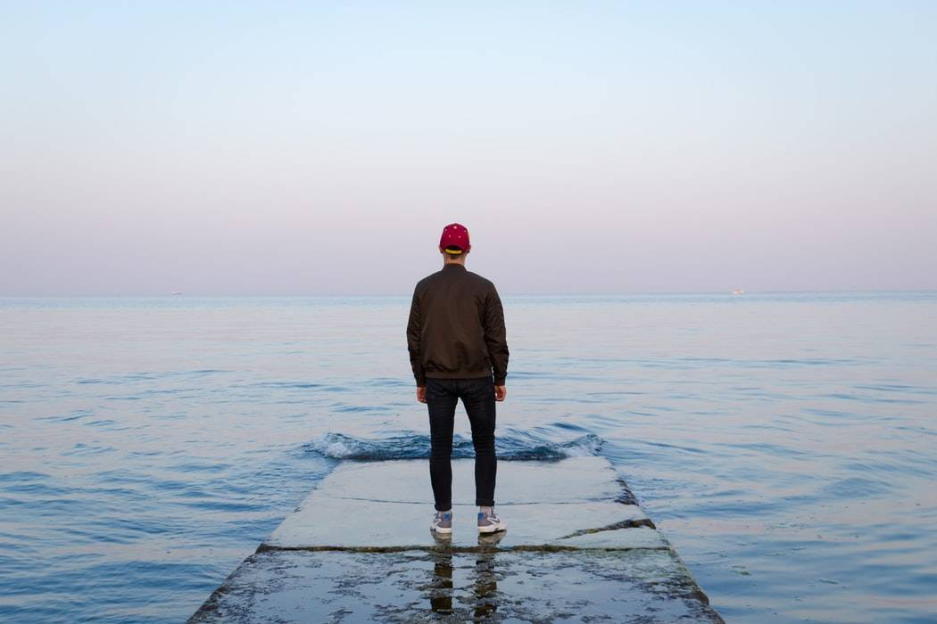 Man standing on a pier staring out at the water and at the beautiful sky