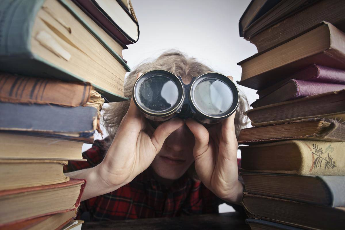 person looking through binoculars surrounded by books