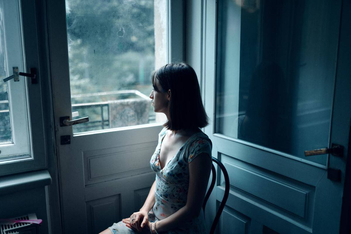 woman seated looking out window