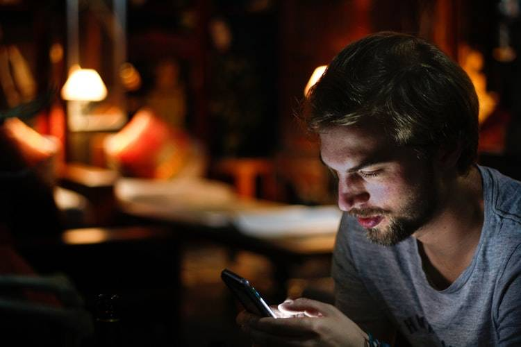 bearded man looking at his phone at home in the evening
