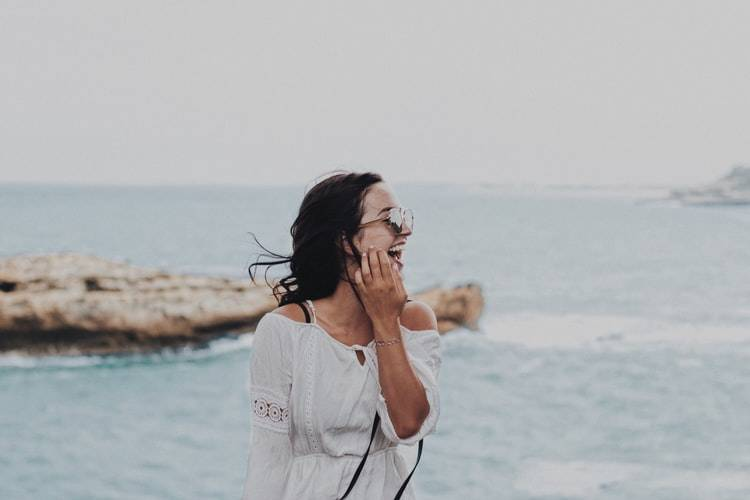 woman in white dress laughing on the beach