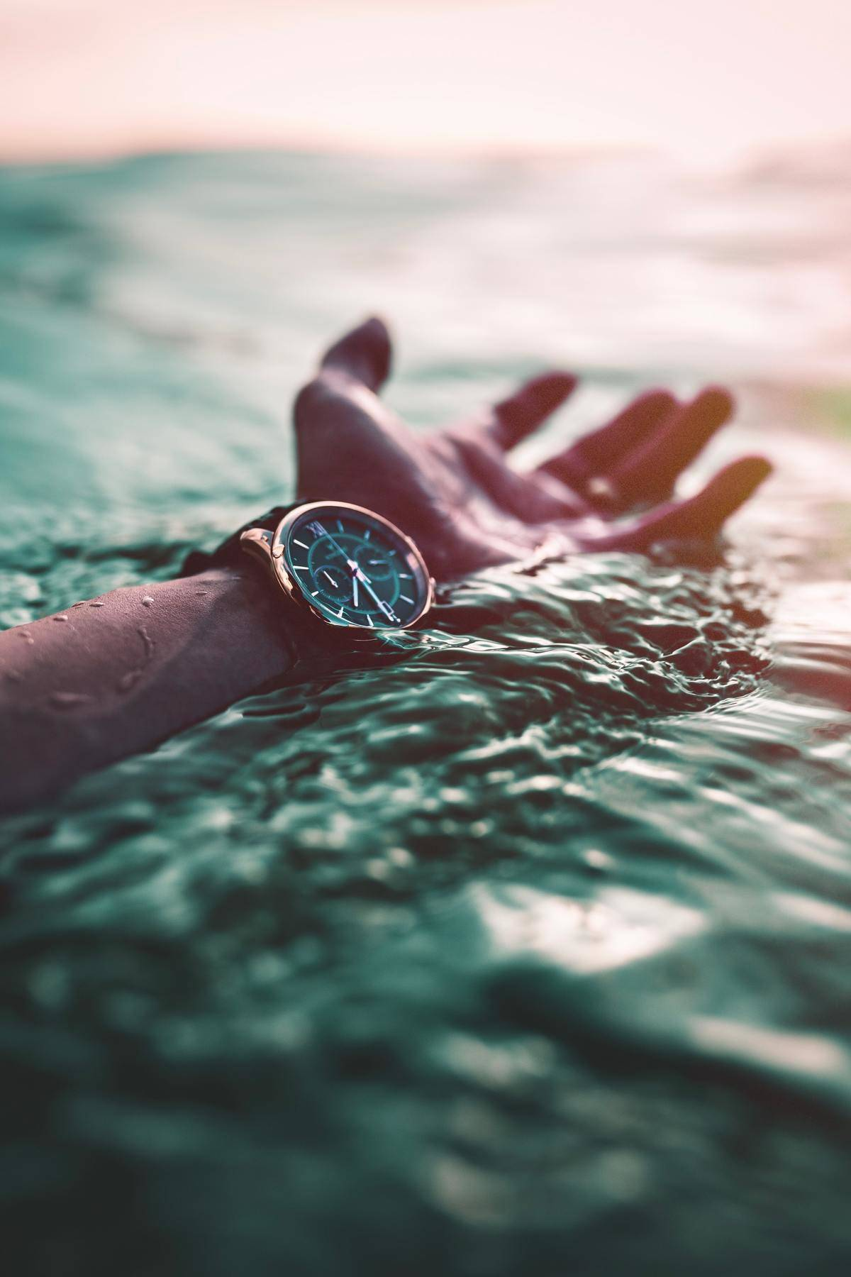putting hand in water with watch on