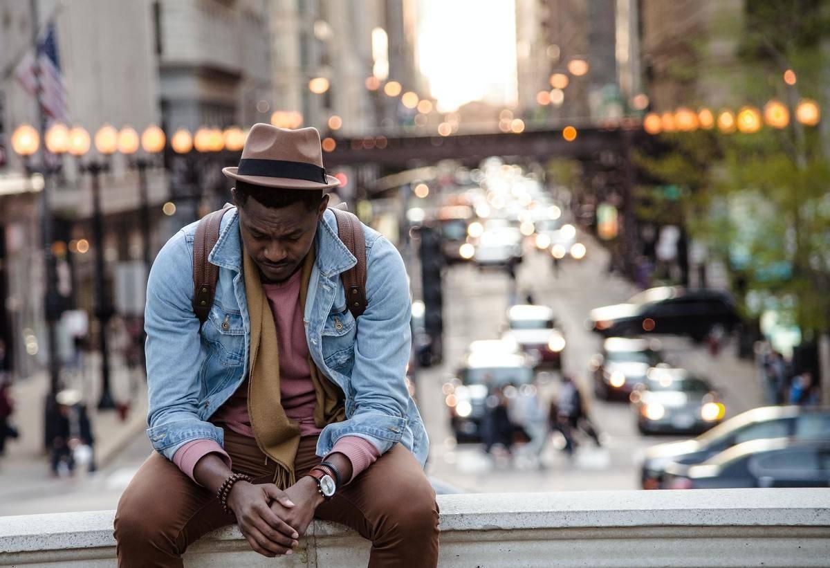 sad man sits on bridge edge in the city