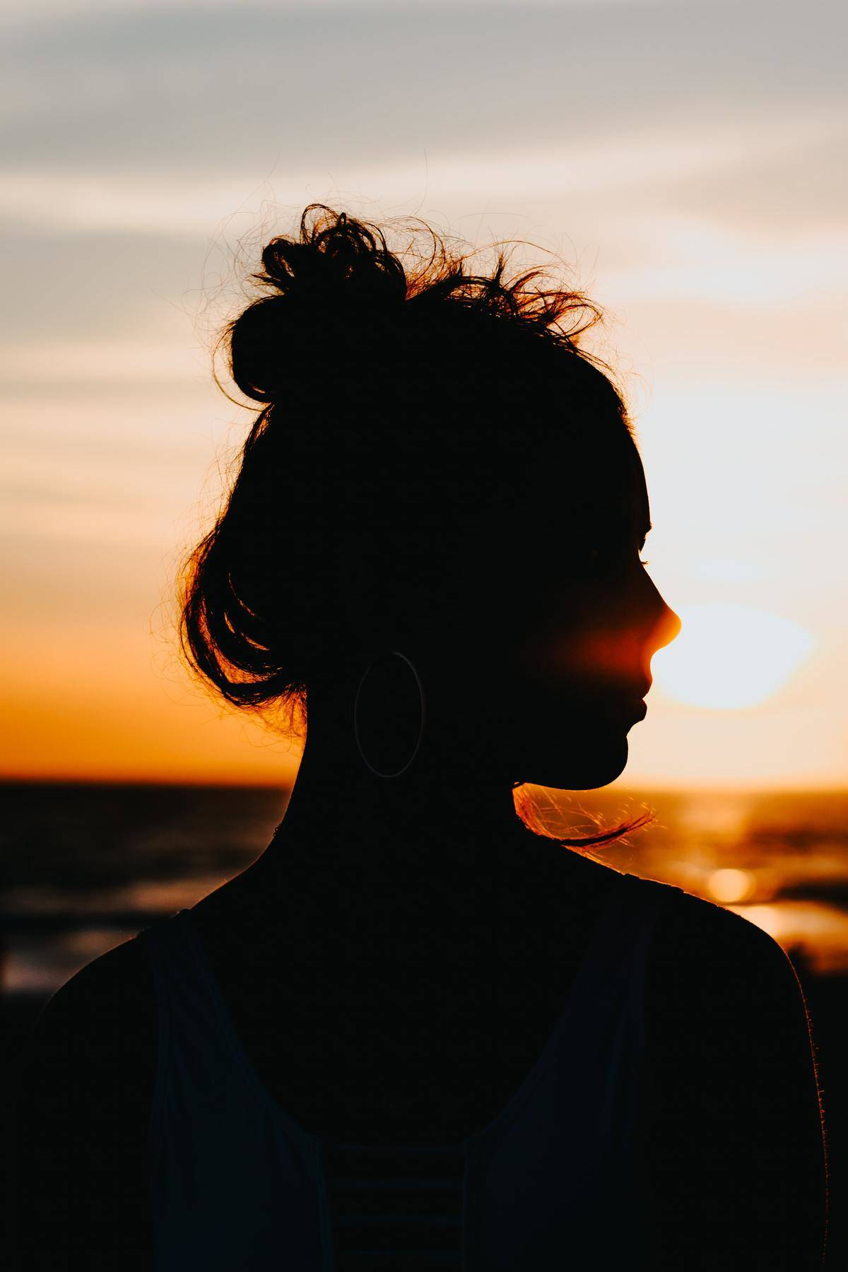 silhouette of woman with hair in messy bun against sunset
