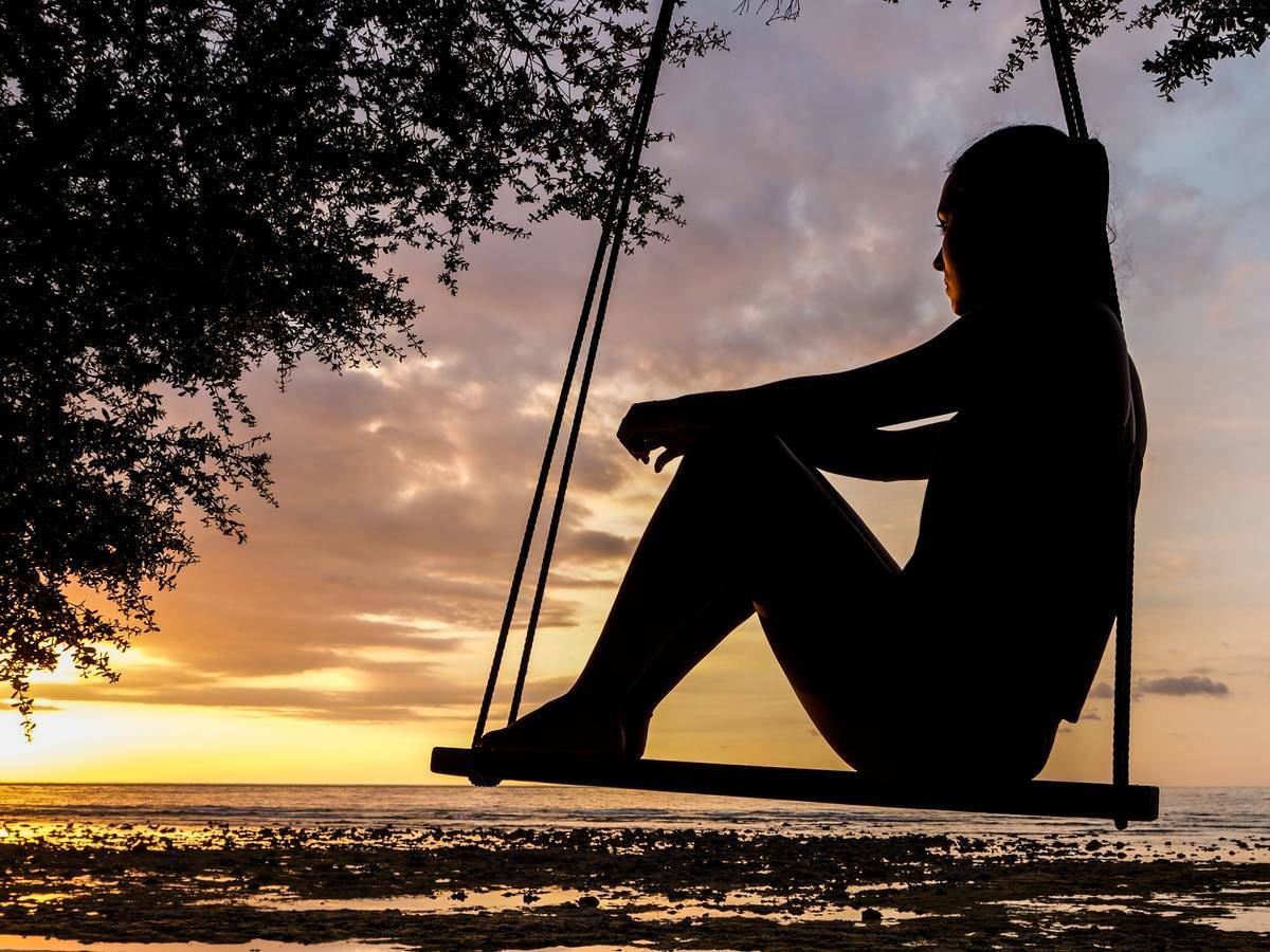 woman sitting on swing looking out over water