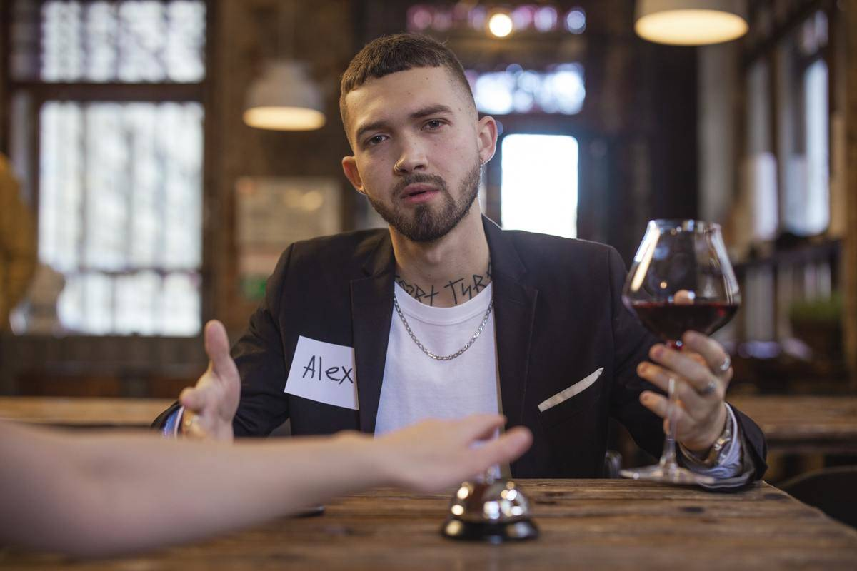man holding wine glass at speed dating
