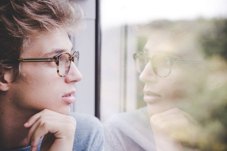 man staring outside a window as his reflection stares back at him
