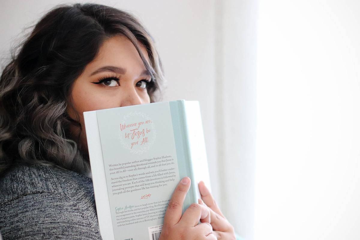 woman peering over top of book