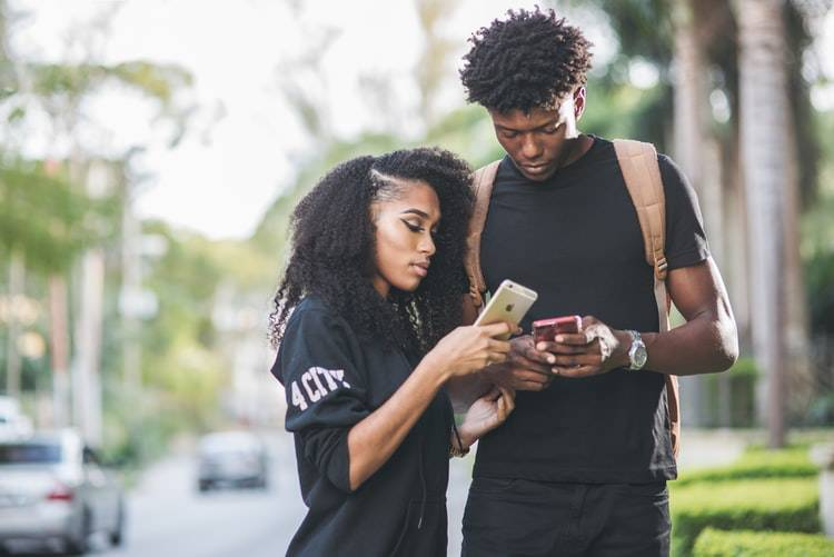 couple standing next to each other looking at something on their cell phones