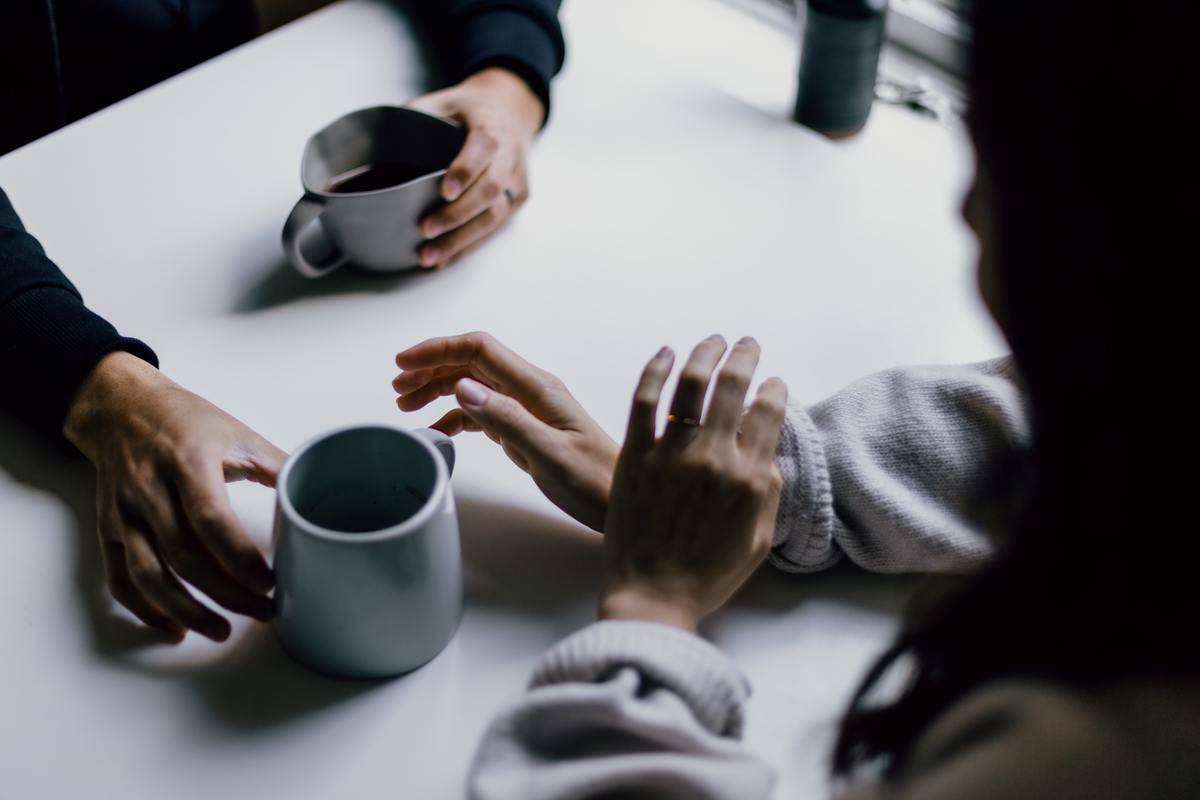 two people talk over coffee at the table