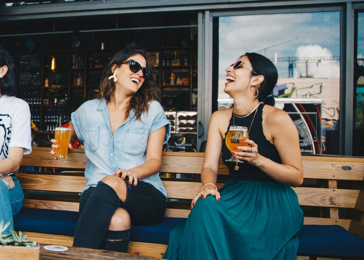 two women laughing while drinking beer on bar bench