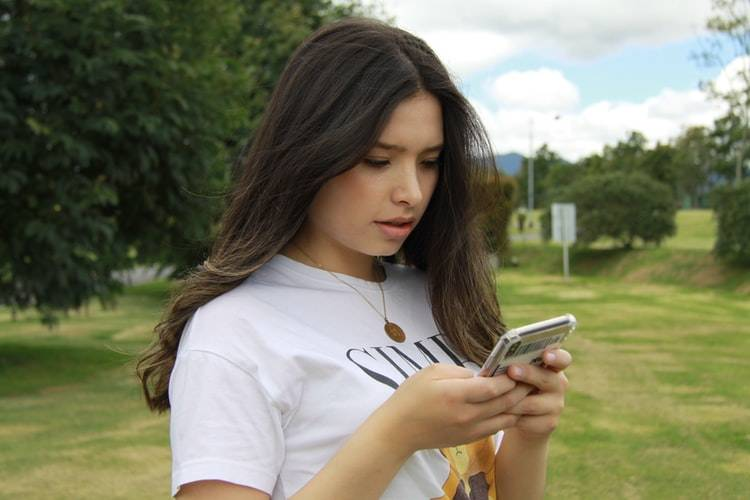 young woman outside on her phone looking shocked at what she's reading