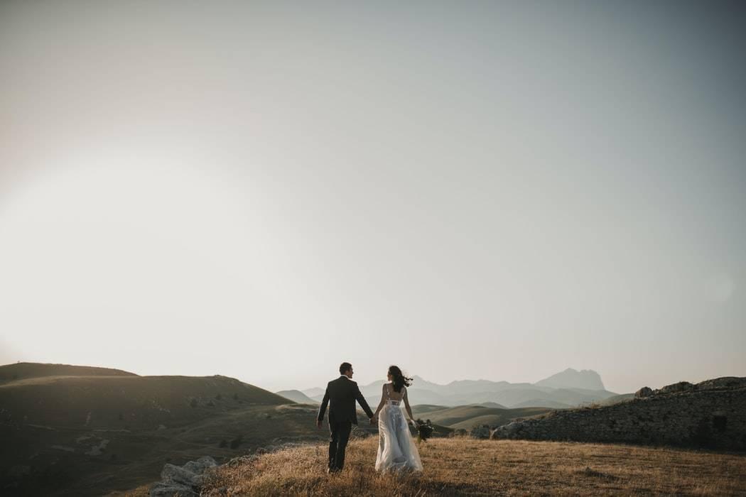 man and woman in wedding attire walking away in a field