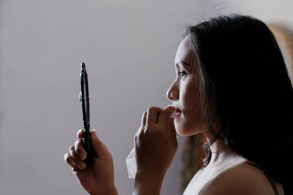 woman applying lipstick in handheld mirror