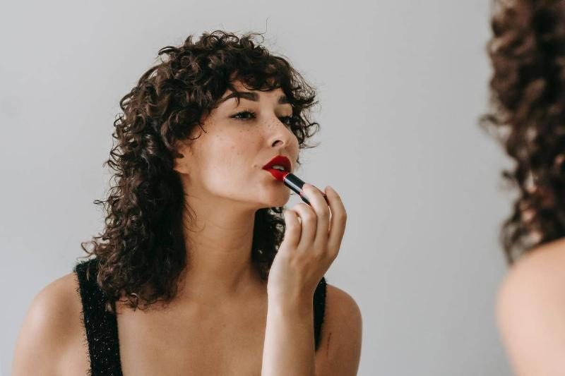 woman applying red lipstick in mirror reflection