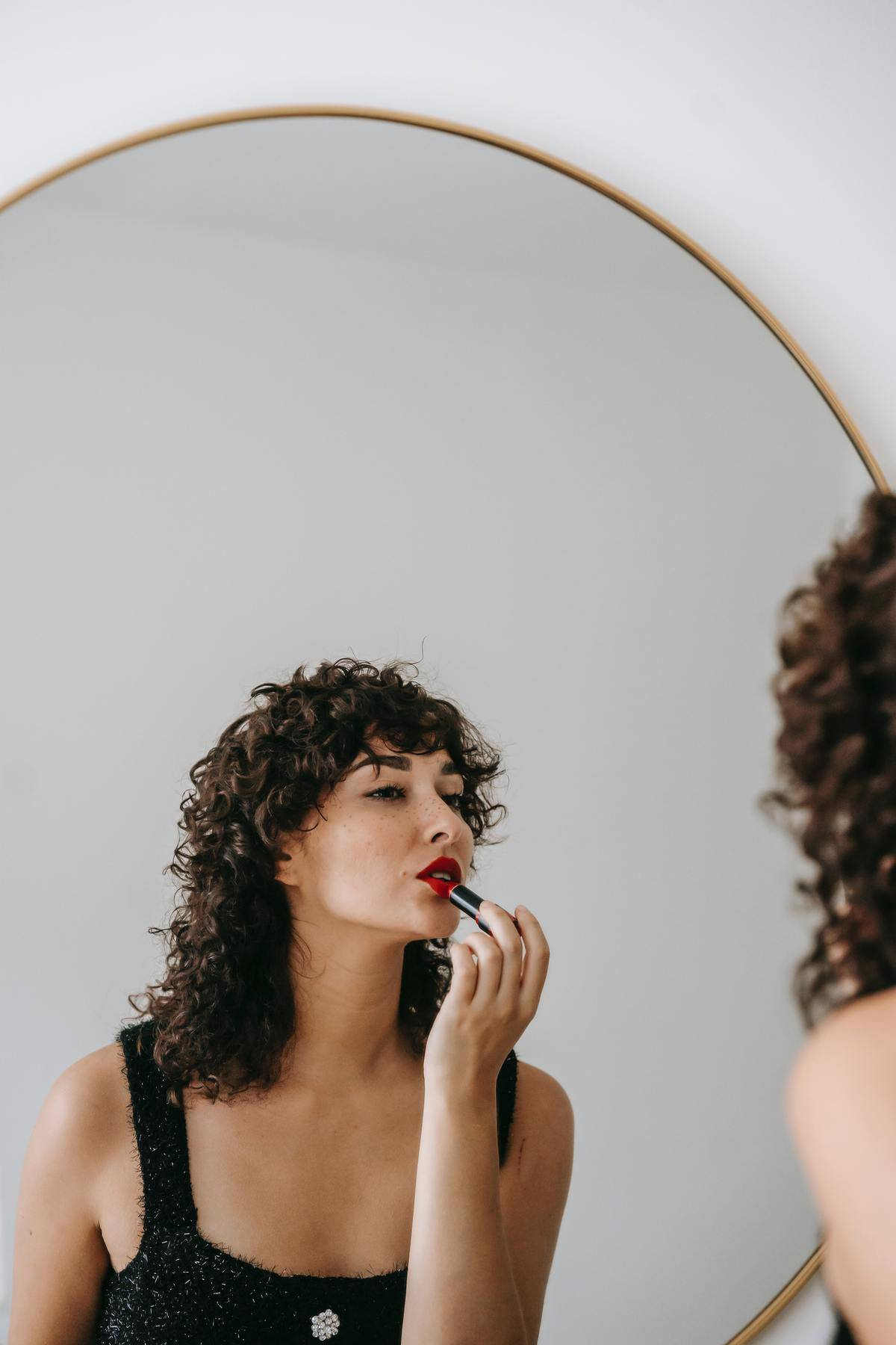 woman putting on her lipstick in the mirror