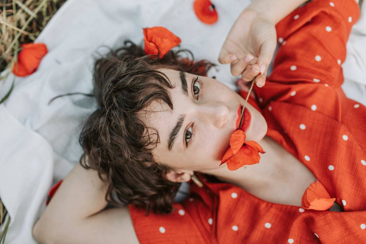 woman laying on picnic blanket with pedals and rose in her mouth