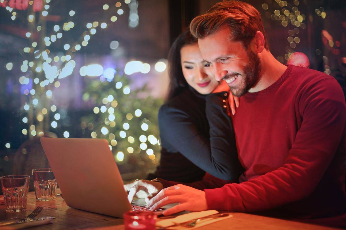 woman leaning on man's shoulder while looking at laptop together