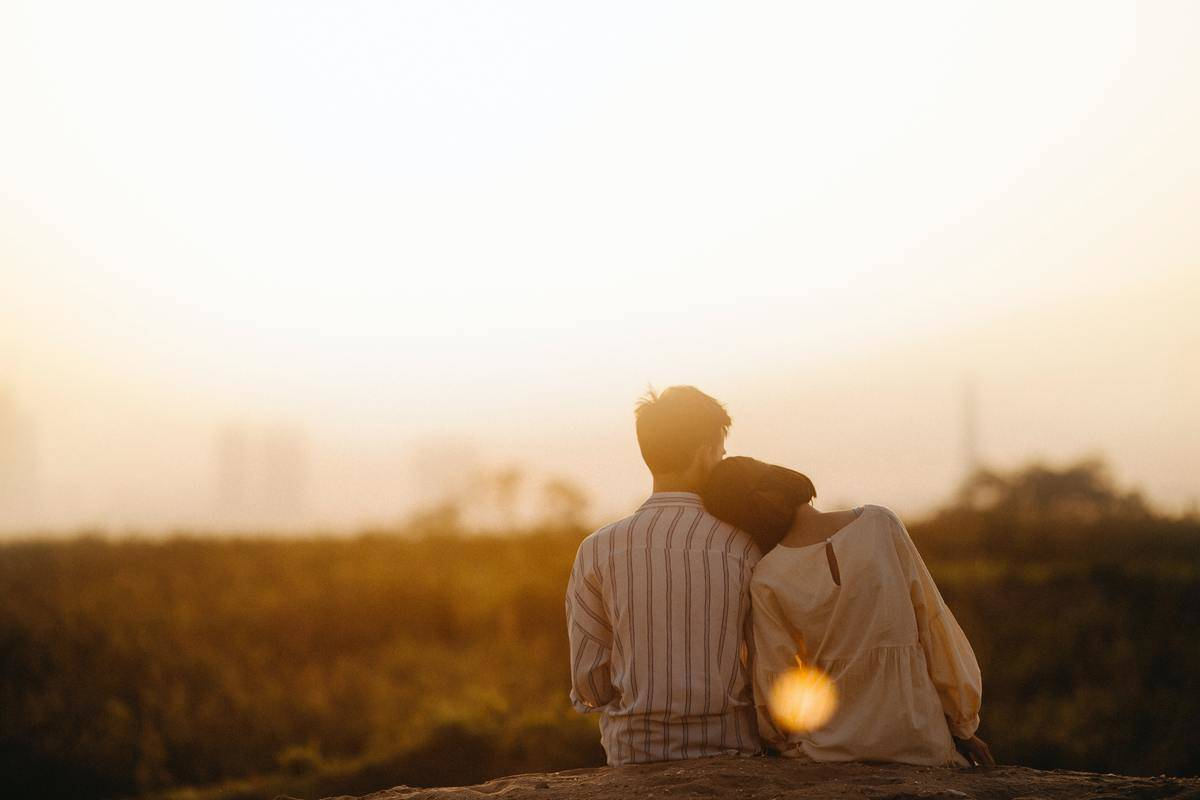 woman leans on man's shoulder in the sunset